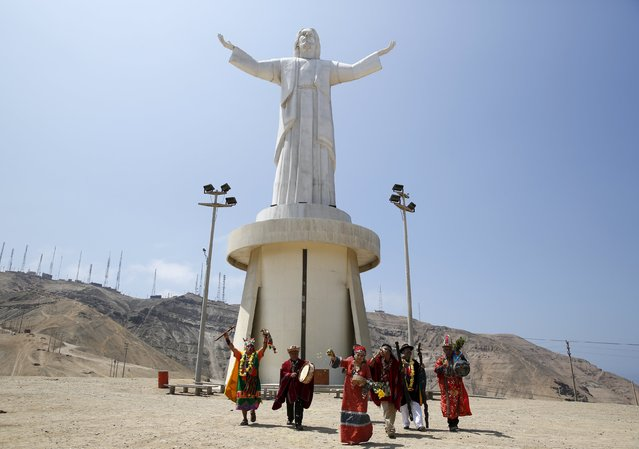 Peruvian shamans perform a ritual of predictions for the new year in front of the 37-meter high statue of 'Christ of the Pacific' at Morro Solar hill in Chorrillos, Lima, Peru, December 29, 2015. (Photo by Mariana Bazo/Reuters)