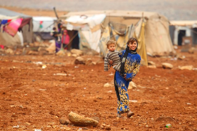 An Internally displaced Syrian youth carries a baby inside a refugee camp in the Hama countryside, Syria January 1, 2016. (Photo by Ammar Abdullah/Reuters)