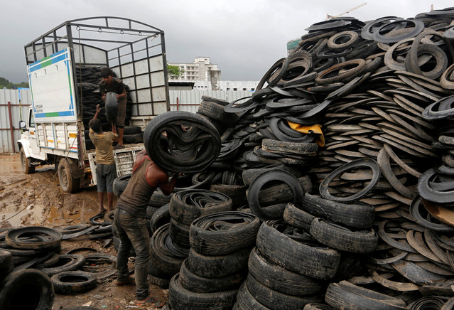 Men unload worn-out rubber tyres from a vehicle at a scrap yard on the outskirts of Mumbai, August 13, 2018. (Photo by Francis Mascarenhas/Reuters)