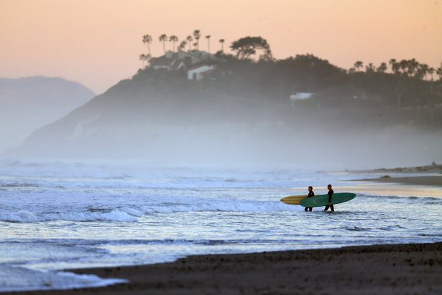 Surfers make their way into the ocean for an early morning surf in Cardiff, California February 12, 2015. Warm Santa Ana winds are expected to push temperatures above 80f in Southern California for the next few days. (Photo by Mike Blake/Reuters)