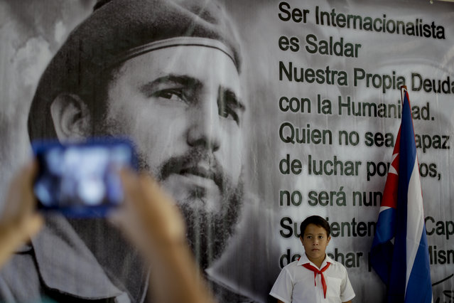 Leona Alarcon posses for a picture beside a poster of late Fidel Castro at memorial in his honor in Guanabacoa on the outskirts in Havana, Cuba, Tuesday, November 29, 2016. Schools and government offices will be closed Tuesday for a second day of homage to Fidel Castro, with the day ending in a rally on the wide plaza where the Cuban leader delivered fiery speeches to mammoth crowds in the years after he seized power. (Photo by Natacha Pisarenko/AP Photo)