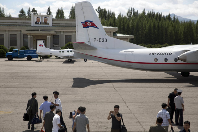 In this Friday, August 17, 2018, photo, passengers alight from a flight at the airport near portraits of late North Korean leaders Kim Il Sung and Kim Jong Il in Samjiyong in North Korea. Samjiyon is one of the main focuses of a massive nationwide construction campaign ahead of North Korea's 70th anniversary in what leader Kim Jong Un has described as a symbolic battle against anyone who would oppose his country. (Photo by Ng Han Guan/AP Photo)
