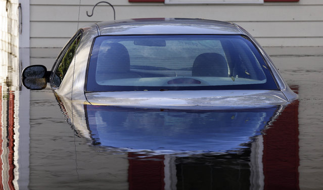 A submerged car sits surrounded by water outside a home in a flooded neighborhood in Lumberton, N.C., Monday, September 17, 2018, in the aftermath of Hurricane Florence. (Photo by Gerry Broome/AP Photo)