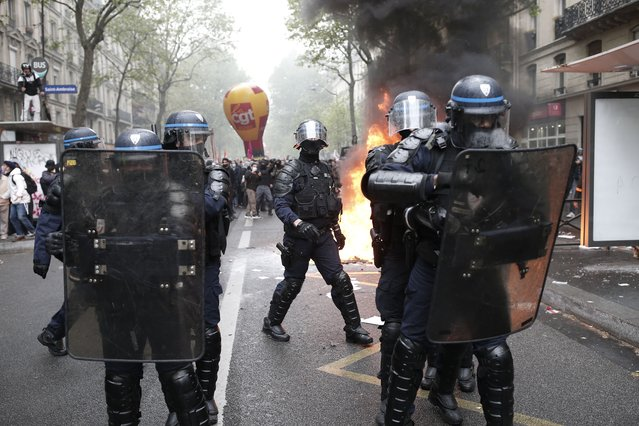 Riot police officers face demonstrators during May Day march incidents Saturday, May 1, 2021 in Paris. Workers and union leaders dusted off bullhorns and flags that had stayed furled during coronavirus lockdowns for slimmed down but still boisterous May Day marches on Saturday, demanding more labor protections amid a pandemic that has turned economies and workplaces upside down. (Photo by Lewis Joly/AP Photo)