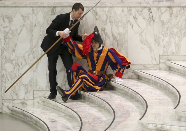 A Swiss Guard who fell ill (R) is helped as Pope Francis leads the weekly audience at the Paul VI hall at the Vatican January 13, 2016. (Photo by Alessandro Bianchi/Reuters)