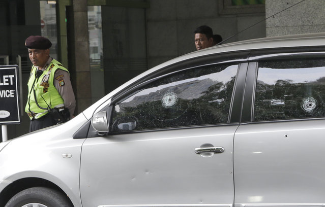 A police officer walks past a car with bullet holes on its windows outside the Starbucks cafe where Thursday's attack occurred in Jakarta, Indonesia, Friday, January 15, 2016. Indonesians were shaken but refusing to be cowed a day after a deadly attack in a busy district of central Jakarta that has been claimed by the Islamic State group. (Photo by Tatan Syuflana/AP Photo)