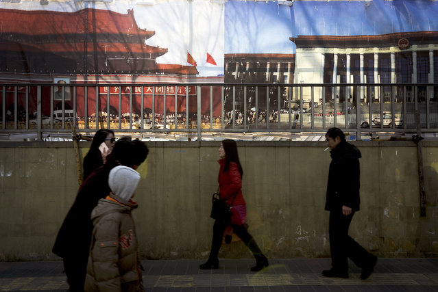 People walk past posters of Tiananmen Gate, left, and the Great Hall of the People on display near a building under construction in Beijing, Tuesday, January 19, 2016. (Photo by Andy Wong/AP Photo)
