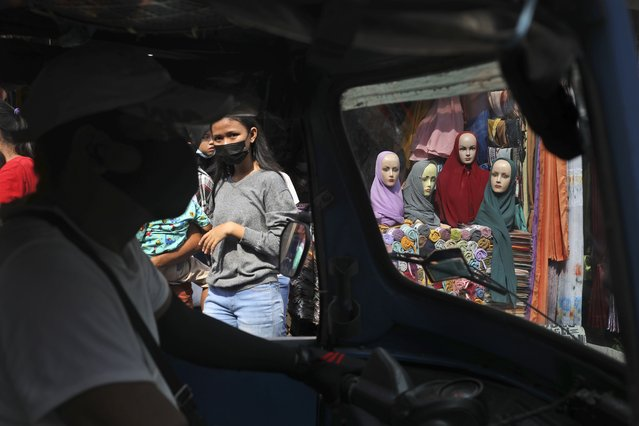"""Mannequins and women wearing masks to curb the spread of coronavirus outbreak are seen through the windows of a three-wheeled motorized taxi called """"bajaj"""", during the last week of Ramadan at a market in Jakarta, Indonesia, Tuesday, May 4, 2021. People flock markets and shopping malls in the capital as they shop for food and new clothings in preparation for Eid al Fitr holiday that marks the end of the holiest month in Islamic calendar. (Photo by Dita Alangkara/AP Photo)"""