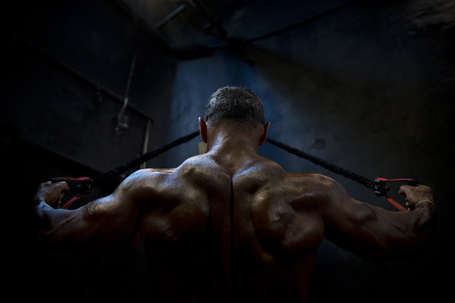 In this Thursday, October 18, 2018 photo, a contestant exercises backstage during the National Amateur Body Builders' Association competition in Tel Aviv, Israel. Dozens of glistening competitors took the stage for the annual body building and fitness competition last week. But behind the scenes, machismo makes way for cooperation. (Photo by Oded Balilty/AP Photo)
