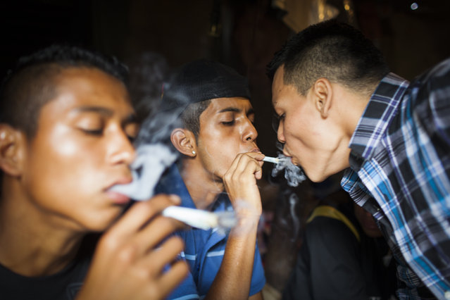 Mara Salvatrucha (MS) gang members smoke marijuana in the Las Victorias district of San Salvador. In March 2012, the two largest gangs in El Salvador – the Mara Salvatrucha (MS) and the Barrio 18 (M18) – agreed on a truce following secret negotiations between gang leaders in prison which were mediated by a bishop and a former rebel leader. It is unclear whether the decision was the idea of the gangs themselves or whether they were encouraged by the government. The murder and kidnapping rate has fallen significantly since the beginning of the truce but it remains unclear how long the truce will hold. (Photo by Adam Hinton)