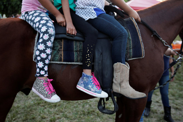 Girls ride a horse during a bull riding event in Santa Tecla, El Salvador, December 15, 2016. (Photo by Jose Cabezas/Reuters)