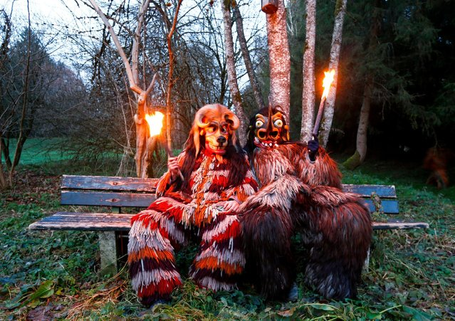 Costumed participants take a break during a traditional Perchtenlauf (Perchten parade) in Osterseeon near Munich, Germany, December 17, 2016. (Photo by Michaela Rehle/Reuters)