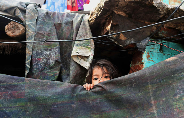 A young Indian girl peeps out from her shanty in a slum in New Delhi on March 18, 2015. (Photo by Money Sharma/AFP Photo)