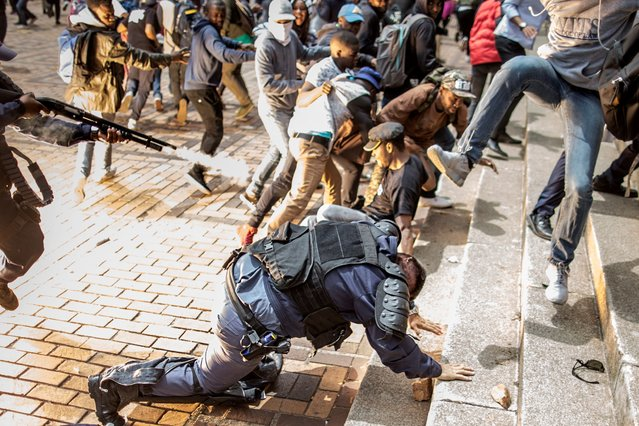 The flash of an exploding stunt grenade is seen while an University of Witwatersrand student jumps on a falling policeman while another policeman discharged his rubber bullet loaded rifle during a running battle with the police forces on campus during a mass demonstration on October 4, 2016 in Johannesburg. South African police fired rubber bullets, stun grenades and teargas at student protesters in Johannesburg as authorities tried to re-open the prestigious Wits University after weeks of demonstrations. The university, along with many campuses across South Africa, has been closed for at least two weeks during protests over tuition fees, with violent clashes regularly erupting between students, police and private security guards. (Photo by Marco Longari/AFP Photo)