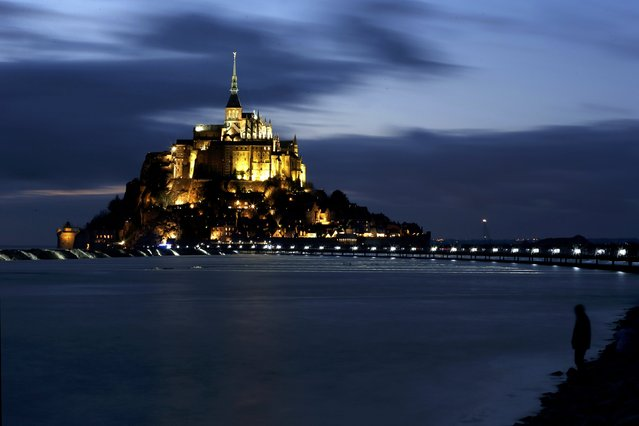 A man stands on an embankment as the incoming high tide surrounds the Mont Saint-Michel 11th century abbey off France's Normandy coast March 21, 2015. (Photo by Pascal Rossignol/Reuters)