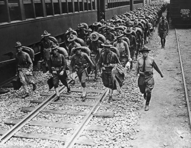 Full-length image of American troops carrying backpacks while walking along train tracks enroute to France from Camp Merritt, New Jersey, World War I, 1916. (Photo by Hulton Archive/Getty Images)