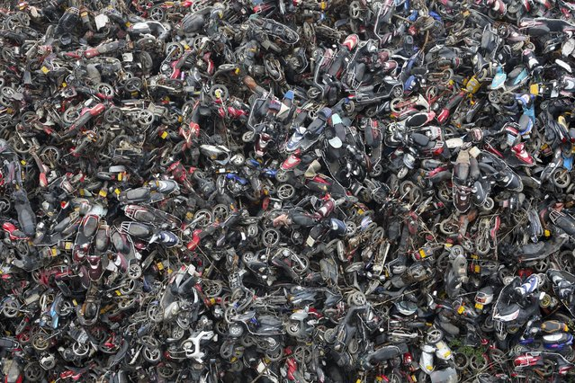 Scrapped motorbikes are piled up at a parking lot used as a scrapyard in Hangzhou, Zhejiang province, March 19, 2015. (Photo by Reuters/China Daily)