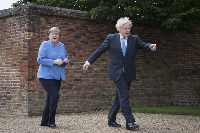 British Prime Minister Boris Johnson shows the way to Chancellor of Germany, Angela Merkel, left, before their bilateral meeting at Chequers, the country house of the Prime Minister of the United Kingdom, in Buckinghamshire, England, Friday July 2, 2021. Johnson is likely to push Angela Merkel to drop her efforts to impose COVID-19 restrictions on British travelers as the German chancellor makes her final visit to Britain before stepping down in the coming months. Johnson will hold talks with Merkel at his country residence on Friday. (Photo by Stefan Rousseau/Pool Photo via AP Photo)