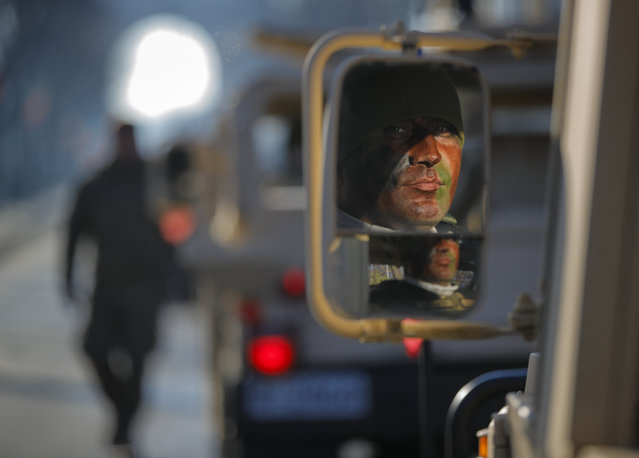 A member of the special operation forces is reflected in the rearview mirror of a vehicle before taking part the military parade in Bucharest, Romania, Saturday, December 1, 2018. (Photo by Vadim Ghirda/AP Photo)