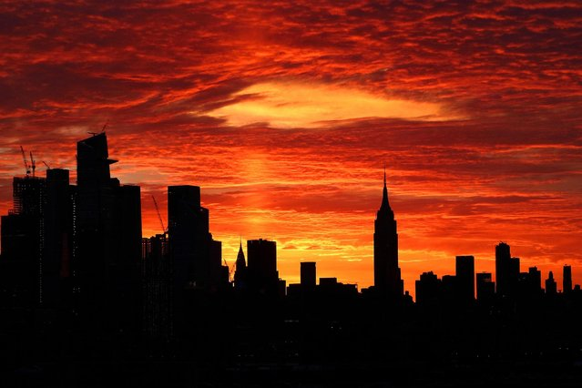 The sky turns orange over midtown Manhattan as the sun rises behind the Empire State Building and Hudson Yards in New York City on March 16, 2021 as seen from Union City, New Jersey. (Photo by Gary Hershorn/Getty Images)