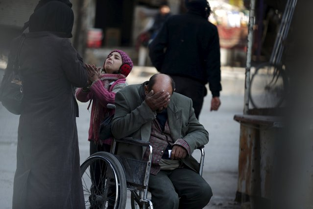 A girl with her father on a wheel chair, ask for help to pay a medical bill from passers by, in Douma, Syria February 3, 2016. (Photo by Bassam Khabieh/Reuters)