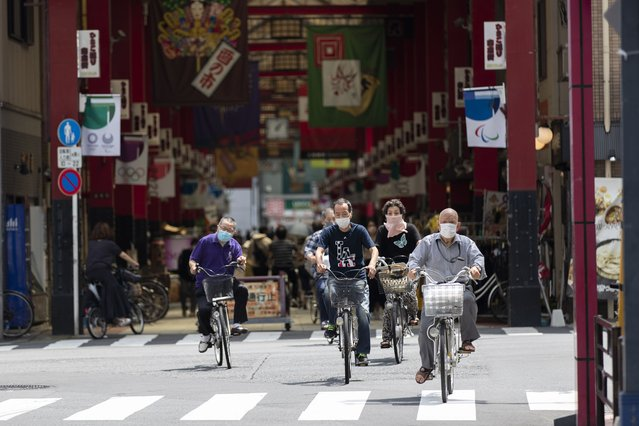 People wearing face masks ride bicycles as they cross an intersection near a shopping street in Tokyo on Thursday, July 15, 2021. (Photo by Hiro Komae/AP Photo)