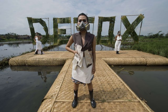 Indonesian models with gas masks wear dresses by Hanna Farhana (C) and Felicia Budi (L and R) during a fashion show in a polluted river basin planted mostly with rice in Rancaekek district near Citarum river located in western Java island as part of a campaign by environmental organization Greenpeace for top international fashion brands to remove toxic chemicals from their supply chains in Indonesia and address water pollution. (Photo by Romeo Gacad/AFP Photo)
