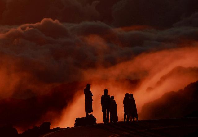 Light illuminates clouds as people watch the sunrise at Haleakala National Park in Hawaii, October 9, 2018. (Photo by Navesh Chitrakar/Reuters)