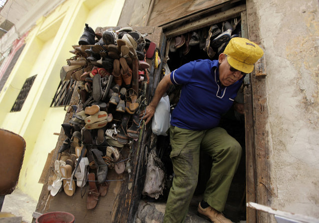 A man comes out of his shoe repair shop in Havana, Cuba, April 2010. (Photo by Desmond Boylan/Reuters)