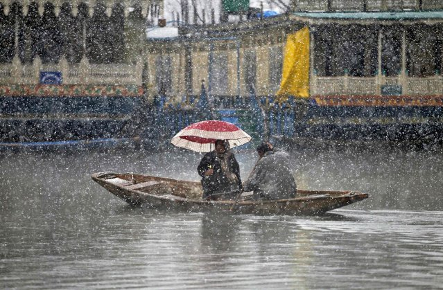 A man rows a boat on the Dal Lake as a woman holds an umbrella during snowfall in Srinagar February 19, 2015. (Photo by Danish Ismail/Reuters)
