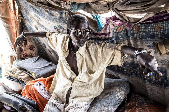 Pape Ndiaye (66), an old waste picker and spokesman for the waste pickers association, rests in his makeshift office in the Mbeubeuss rubbish dump in Dakar on July 14, 2021. (Photo by John Wessels/AFP Photo)