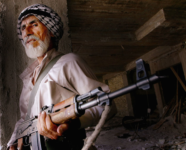 An Iraqi Shiite man loyal to the radical Shiite cleric Moqtada al-Sadr holds his AK 47 during the fighting on August 6, 2004 in Najaf, Iraq. (Photo by Ghaith Abdul-Ahad/Getty Images)