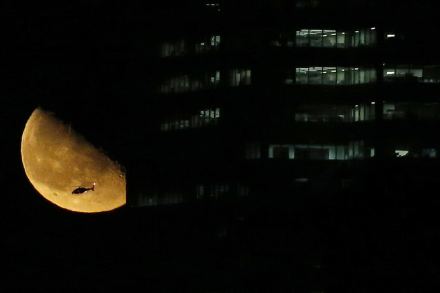 A helicopter flies over New York City as the moon rises near a building seen from Jersey City, N.J., Friday, March 13, 2015. (Photo by Julio Cortez/AP Photo)