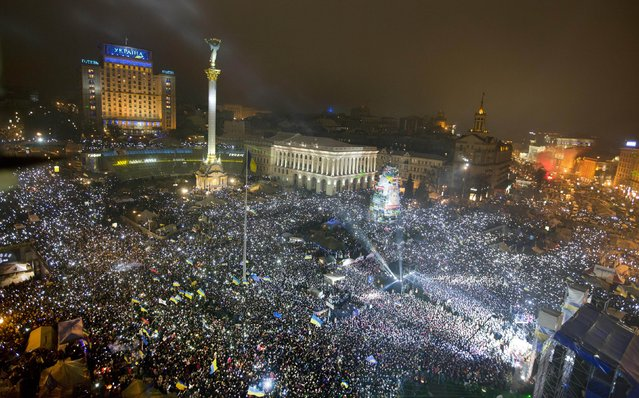 Pro-European Union activists hold light as they sing the Ukrainian national anthem, celebrating the New Year in the Ukrainian capital Kiev's main square early Wednesday, January 1, 2014. At least 100,000 Ukrainians sang the country's national anthem together at the square on New Year's Eve in a sign of support for integration with Europe. (Photo by Efrem Lukatsky/AP Photo)