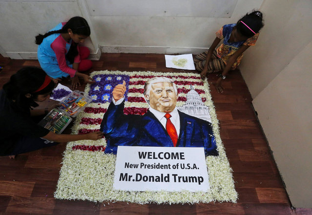 Students of an art school apply finishing touches to a portrait of President elect Donald Trump, made of oil pastel paints and decorated with flowers, before his swearing-in ceremony, in Mumbai, India, January 20, 2017. (Photo by Shailesh Andrade/Reuters)