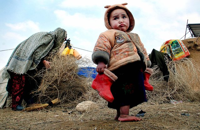 A child holds his boots in a camp for the internally displaced on the outskirts of Mazar-e Sharif, north of Kabul, Afghanistan, on January 6, 2014. Mazar-e Sharif has been experiencing snow and below freezing weather. (Photo by Mustafa Najafizada/Associated Press)
