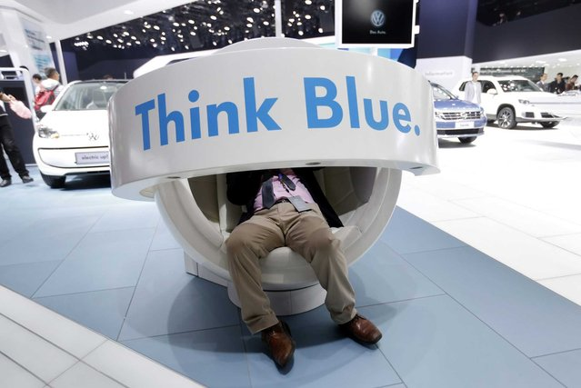 "A visitor sits in a Volkswagen ""Think Blue"" slogan chair at the 16th Shanghai International Automobile Industry Exhibition in Shanghai, China, 20 April 2015. (Photo by How Hwee Young/EPA)"