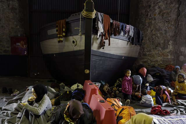 Afghan migrants rest  near a boat that is being stored at a warehouse, which is used as a shelter for refugees and migrants at the Athens' port of Piraeus, on Monday, February 29, 2016. Border restrictions further north in the Balkans have left thousands of refugees and other migrants stranded in a country that is still wracked by its own financial crisis and unable to seal its lengthy sea border with Turkey. (Photo by Thanassis Stavrakis/AP Photo)