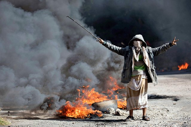 A Yemeni man flashes the V for victory sign next to burning tires during protests calling for the removal of the Saudi-backed coalition government and deteriorating economic and living conditions, in Yemen's third city of Taez on September 27, 2021. (Photo by Ahmad Al-Basha/AFP Photo)
