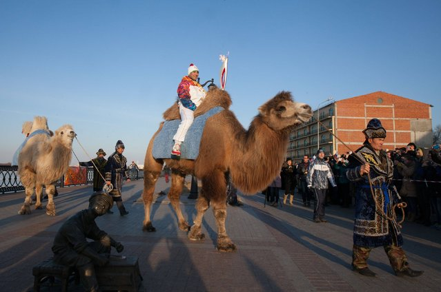 In this photo taken on Sunday, January 26, 2014 and provided by Olympictorch2014.com, an Olympic torch bearer Dmitry Slaschev, top, rides a camel holding an Olympic torch during the torch relay in  the southern Russian city of Astrakhan. (Photo by AP Photo/Olympictorch2014.com)