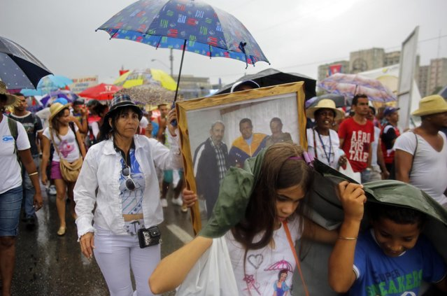 Cubans march in the rain on Revolution Square marking May Day, in Havana, Cuba, Friday, May 1, 2015. (Photo by Ramon Espinosa/AP Photo)