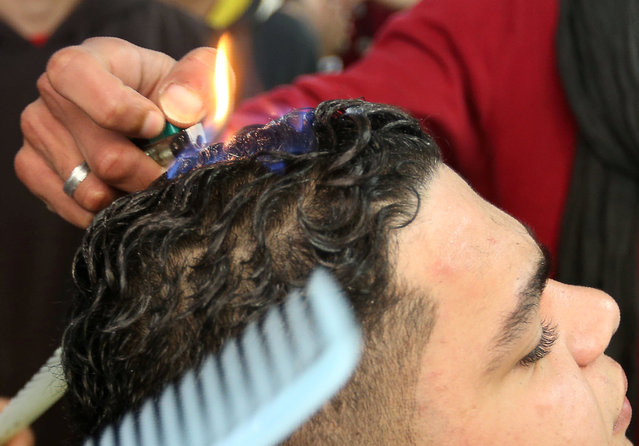An assistant to Palestinian barber Ramadan Odwan uses the flame from a lighter as he styles and straightens the hair of a customer with fire at his salon in Rafah, in the southern Gaza Strip February 5, 2017. (Photo by Ibraheem Abu Mustafa/Reuters)
