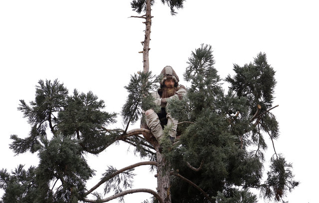A man sits near the top of a sequoia tree Wednesday, March 23, 2016, in downtown Seattle. Authorities were alerted to the unidentified man in the tree Tuesday morning and he was still clinging to its branches nearly a day later. (Photo by Elaine Thompson/AP Photo)