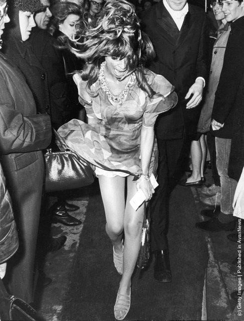 British actor Julie Christie's dress flies up during a wind gust while walking with her date, Don Bessant, at the Odeon Cinema in Marble Arch