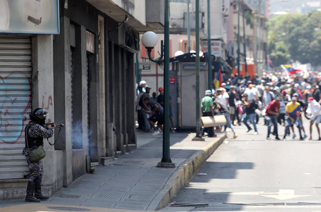 A government security forces member fires his weapon during clashes with protesters in Caracas, Venezuela April 30, 2019. (Photo by Manaure Quintero/Reuters)