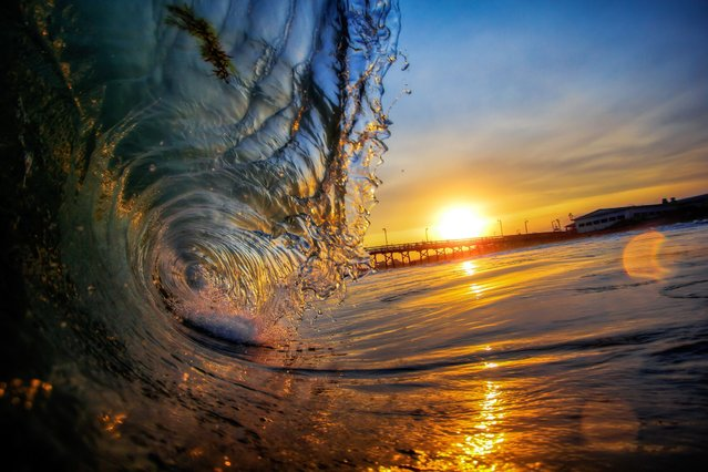 Smooth glass-like waves arrive gently into the shore, reflecting the setting sun's stunning golden rays. (Photo by Brad Styron/Solent News & Photo Agency)