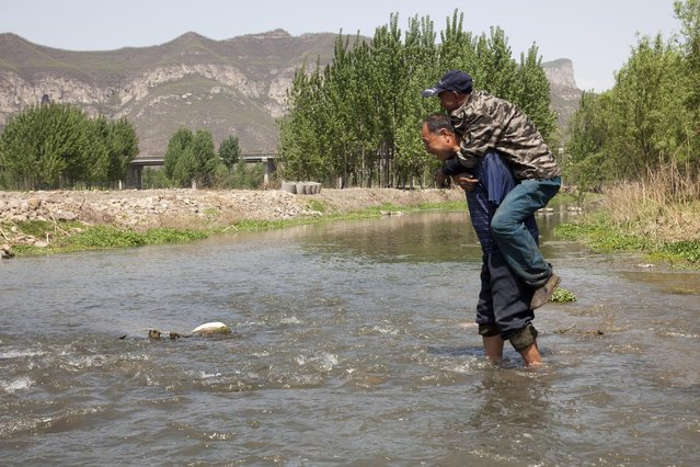 In this April 23, 2015 photo, Jia Wenqi carries his friend Jia Haixia on his back across a stream in Yeli village near Shijiazhuang city in northern China's Hebei province. (Photo by Helene Franchineau/AP Photo)