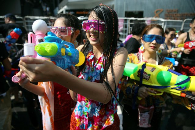People play with water guns during Songkran Water Festival to celebrate Thai New Year, in Bangkok, Thailand on April 14, 2019. (Photo by Soe Zeya Tun/Reuters)