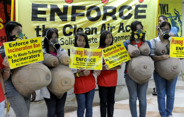 """Women donning """"pregnant bellies"""" and gas masks stand in front of a banner calling for the Clean Air Act to be enforced, ahead of International Women's Day, in suburban Manila on March 7, 2014. Environment and health advocates called for the protection of women against pollutants, during a conference organized by the EcoWaste Coalition to dramatize the adverse health impact of burning trash. (Photo by Jay Directo/AFP Photo)"""