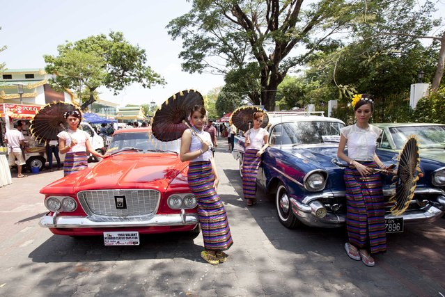 Myanmar models wearing traditional dresses pose for photo near old cars displayed at the first Myanmar Classic Car Show organized by Myanmar Classic Car Club at Myanmar Culture Valley Saturday, May 9, 2015, in Yangon, Myanmar. (Photo by Khin Maung Win/AP Photo)